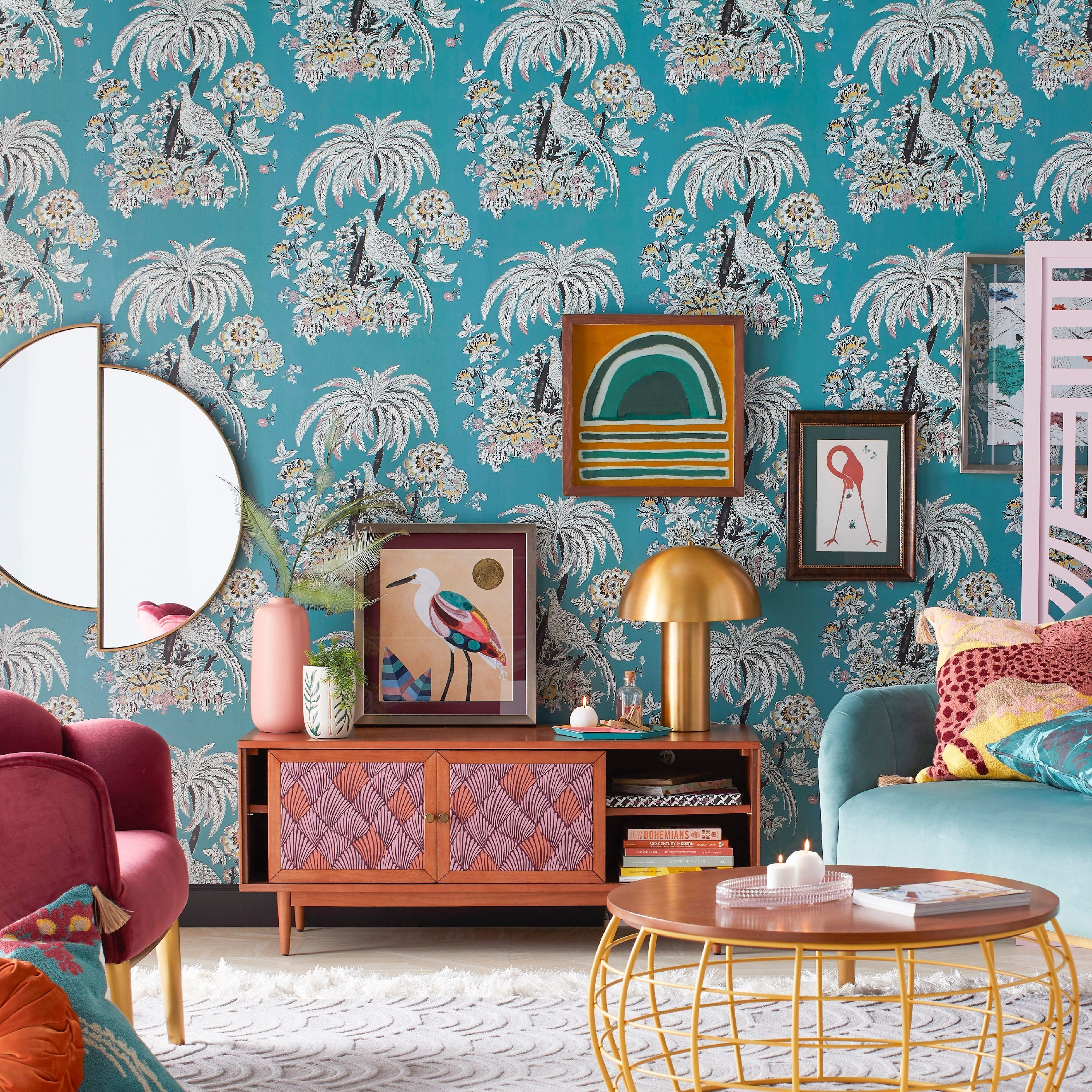 blue wall paper with a pattern of a palm tree, flowers, and a peacock all over it