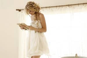 Taylor Swift standing on a bed reading in a white dress