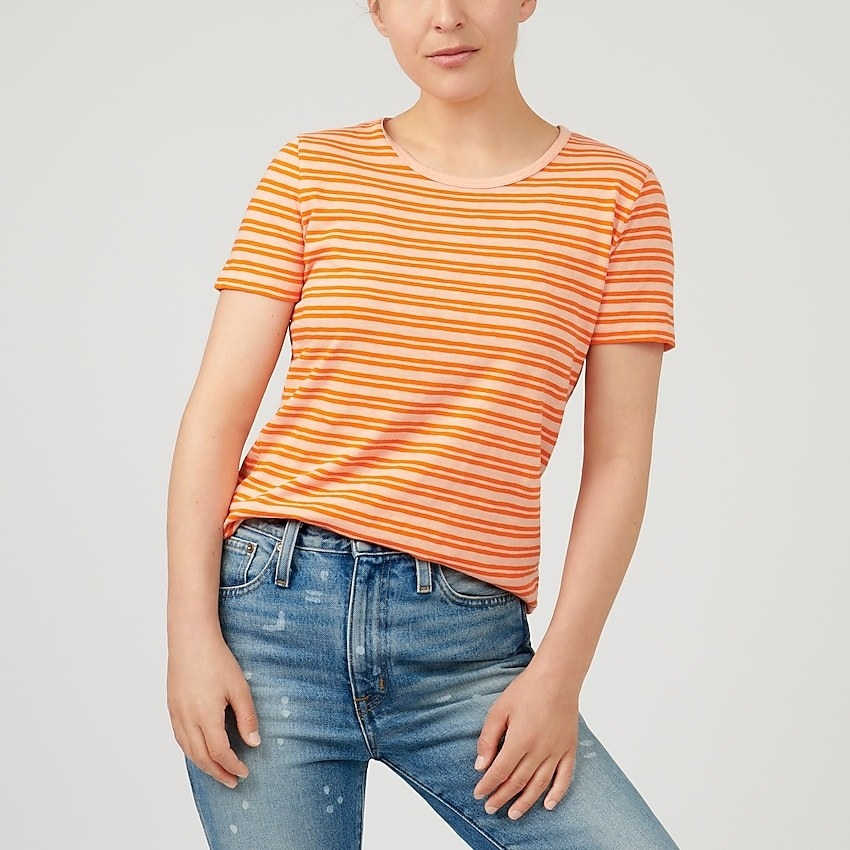 model in orange, light orange, and yellow striped tee