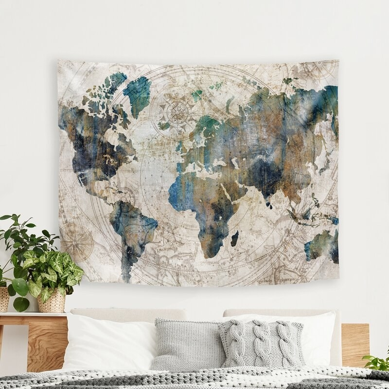 The tapestry with a cream background and a design that looks like a world map using colors like light blue, navy blue, and dark green