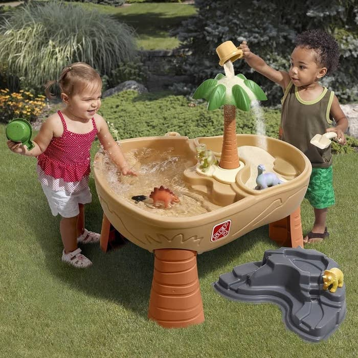 two toddlers playing with the table which is filled half with water and half with sand