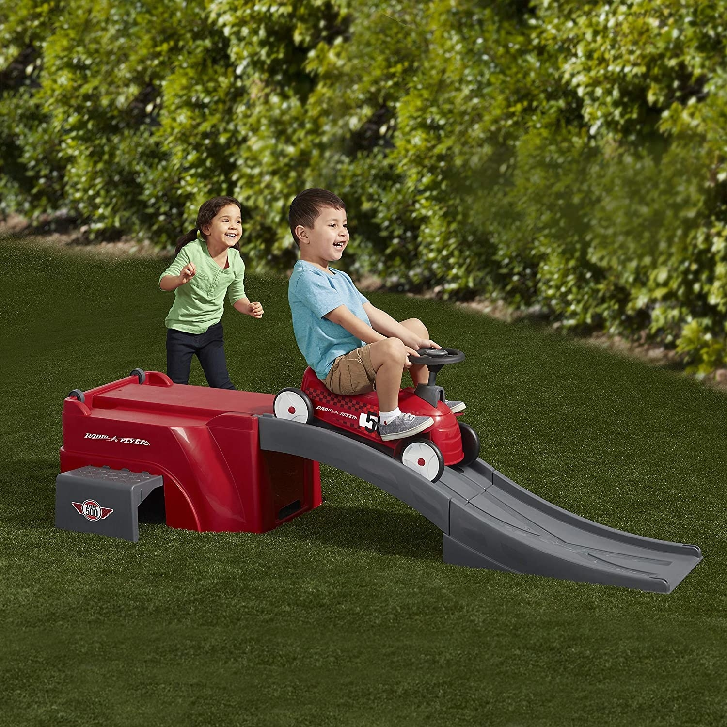 two kids playing, one is sitting on the radio flyer car gliding down a ramp