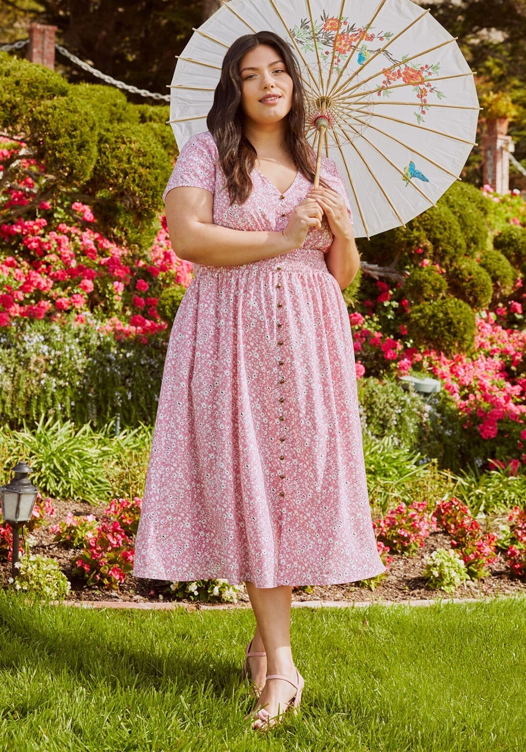 model wearing V-neck pink floral dress with decorative buttons