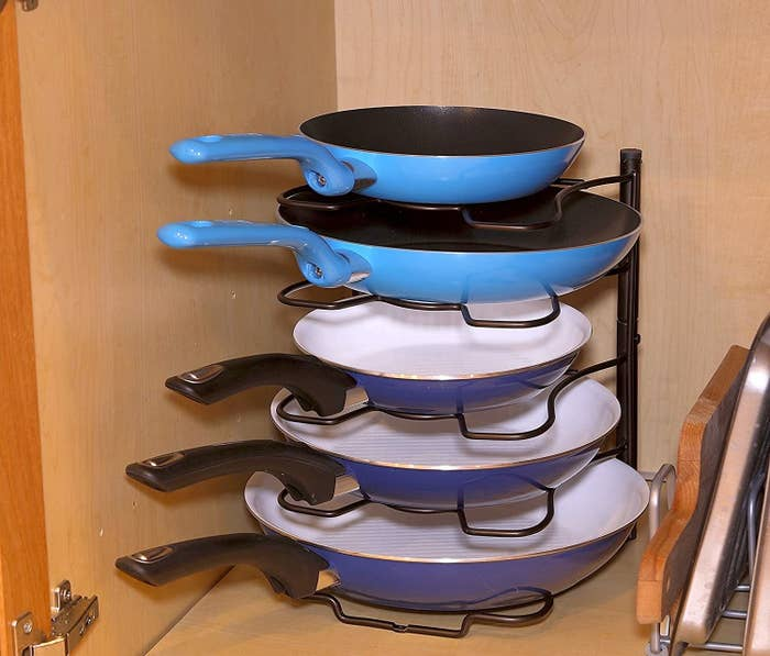A rack holding up five different sizes pans in a cabinet