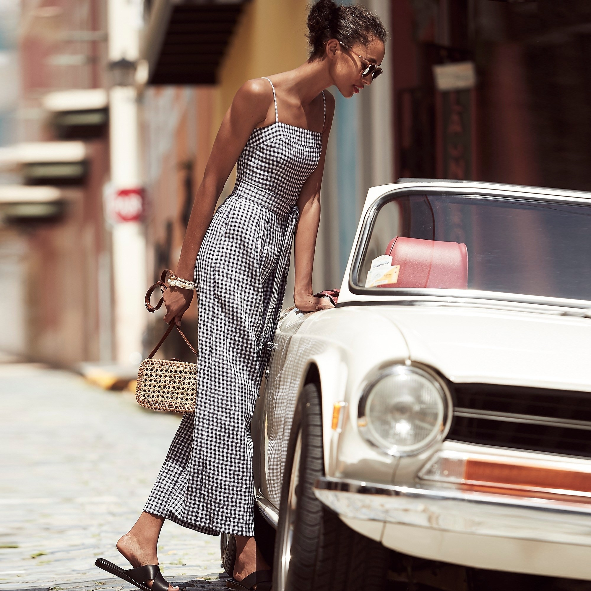 model in black and white gingham jumpsuit with long pants, spaghetti straps, and a high waist