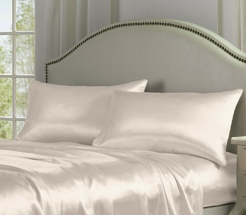 The ivory sheets and pillowcases with a silky, smooth-looking texture styled on a bed