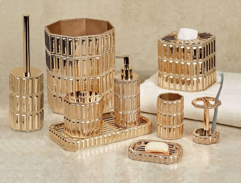 The bathroom counter set with a gold-toned finish. The set includes a soap dispenser, tissue box, soap dish, toothbrush holder, and more