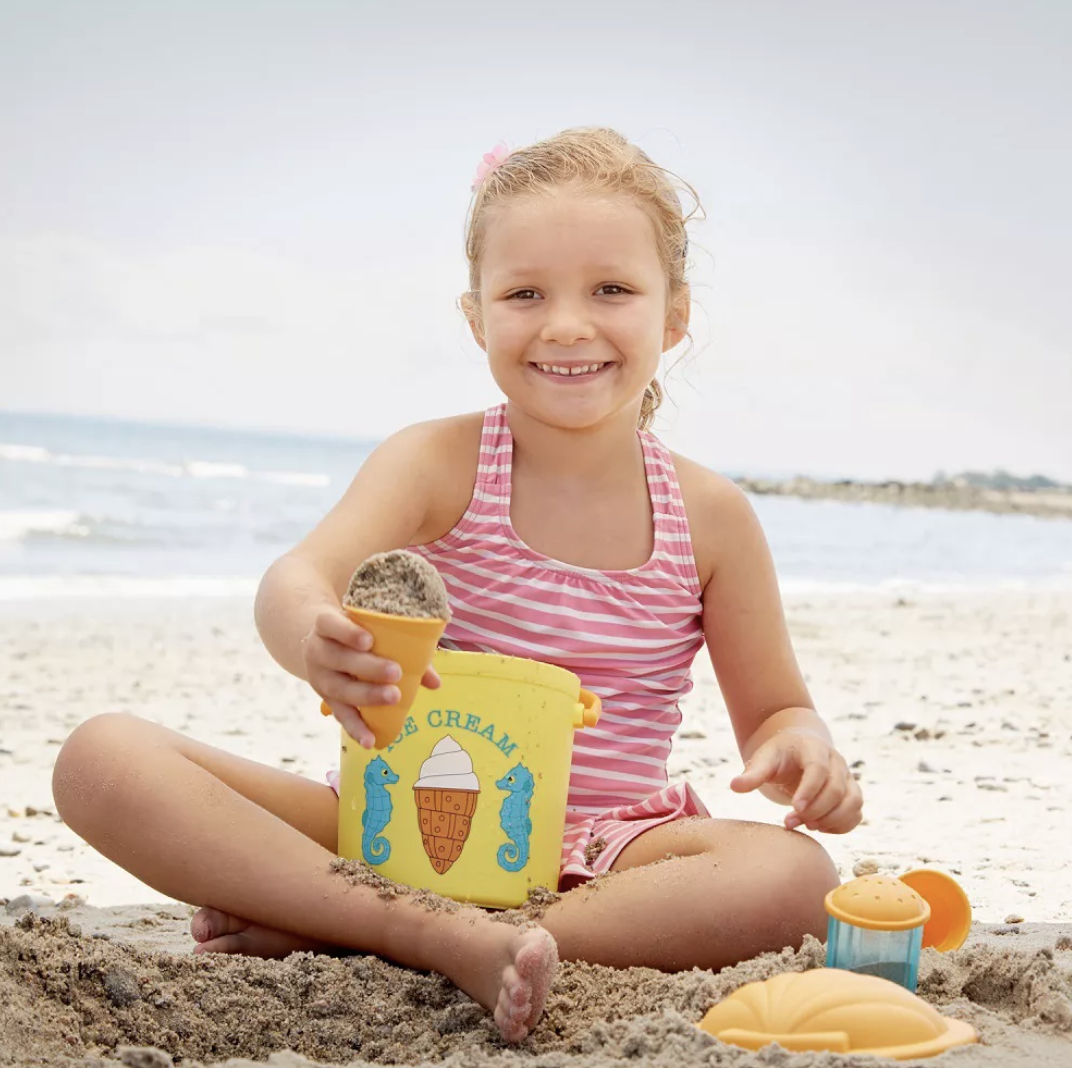a child holding an ice cream cone of sand and a bucket