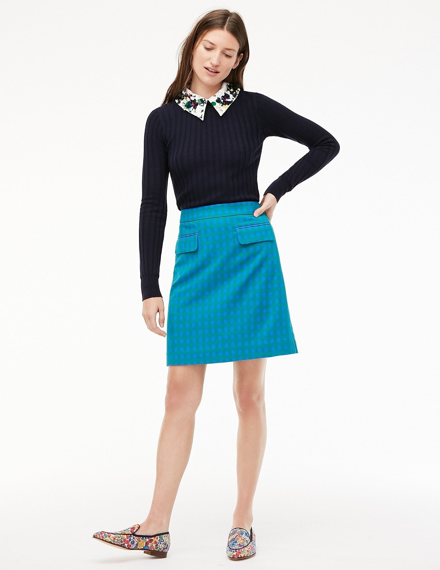 model in teal and green plaid mid thigh skirt with two front pocket flaps