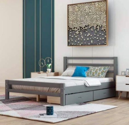 Gray bed with two drawers underneath against a white wall with a drip painting