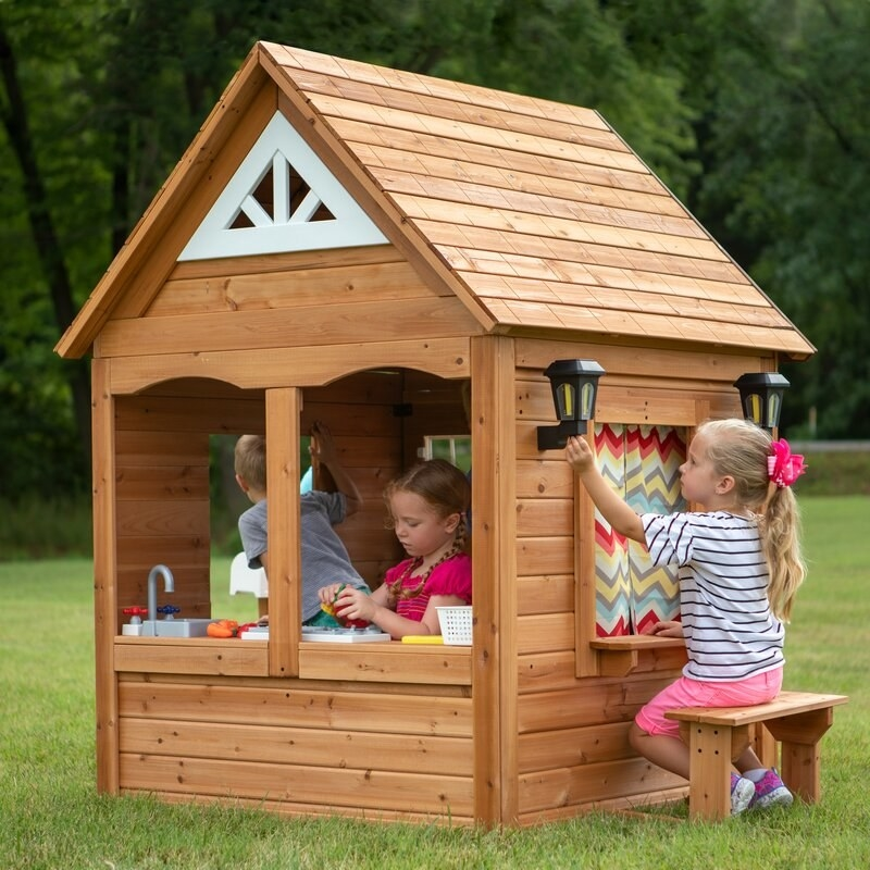 three kids playing inside a well built wooden play house with a curtain and a full kitchen inside