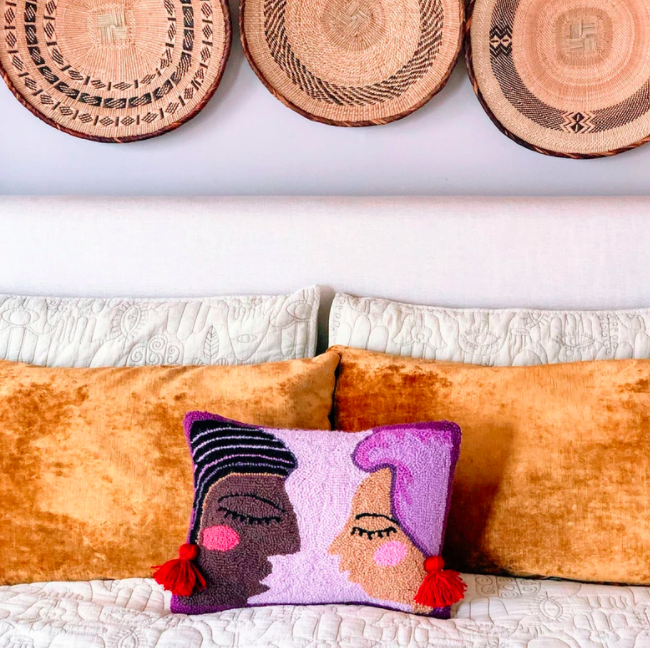 A purple pillow with embroidered faces next to an orange pillow and white sheets