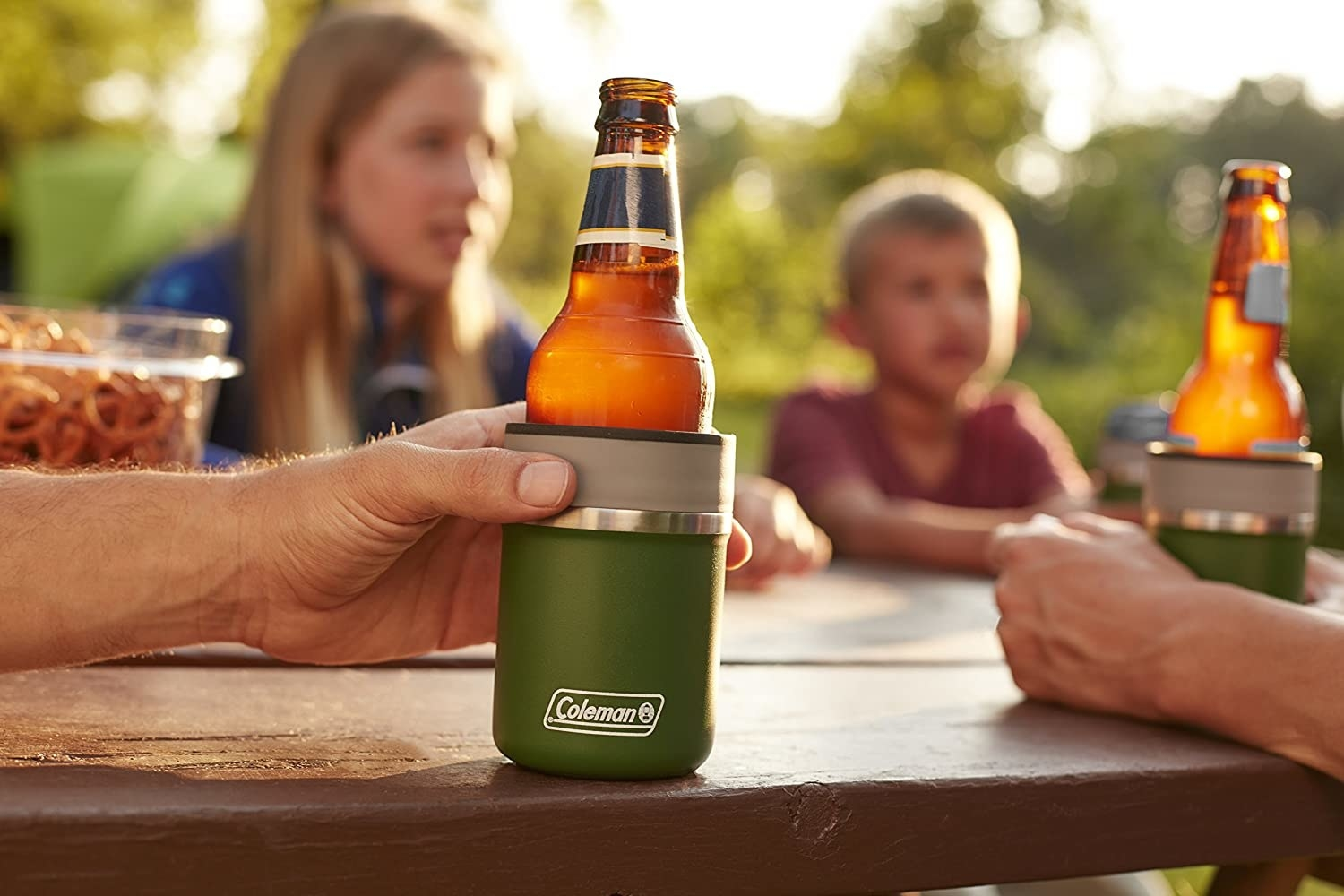People sit at a picnic table with a bottle in a coozie