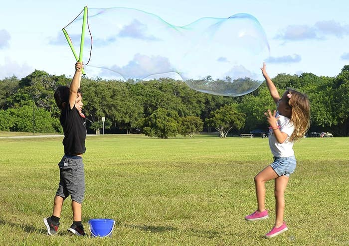 two kids playing with a massive bubble from the wand