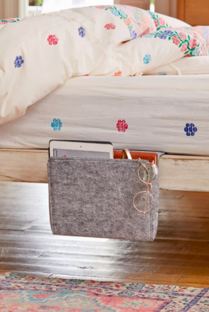 Gray bedside caddy with gold glasses and a tablet on the side of the bed