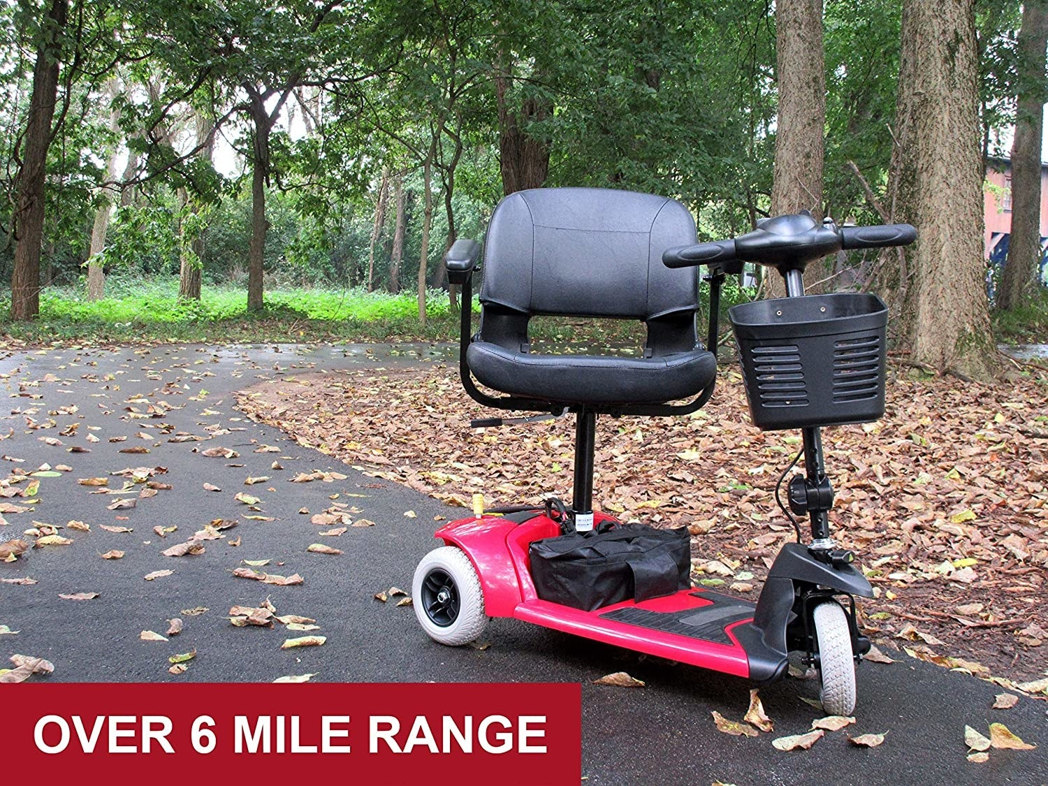 a three wheeled mobility electric scooter with a cushioned seat and basket at the front parked on a sidewalk in a park full of leave