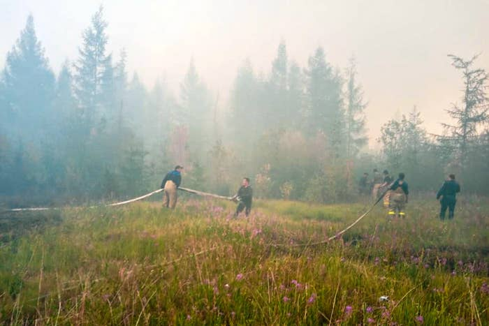 Firefighters carry hoses and extinguish fires near the village of Batagay, Sakha Republic, in Russia