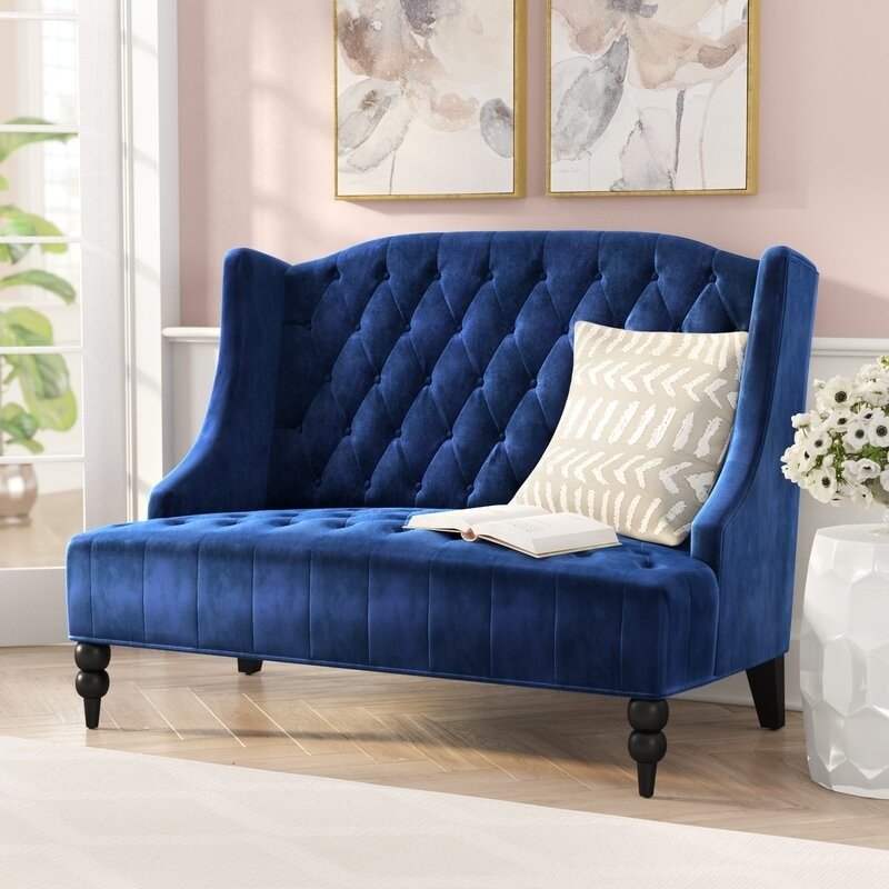 The sofa with a blue velvet texture, tufted back and seating, and short, black lacquered legs