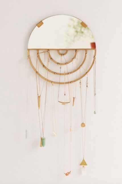 Half circle hanging mirror with various pendant necklaces on a bare white wall