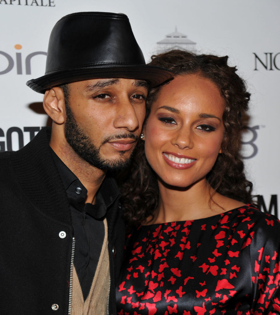 Swizz Beatz (wearing a leather fedora) with his cheek pressed up against Alicia Keys (who is wearing a black dress with red butterflies on it).