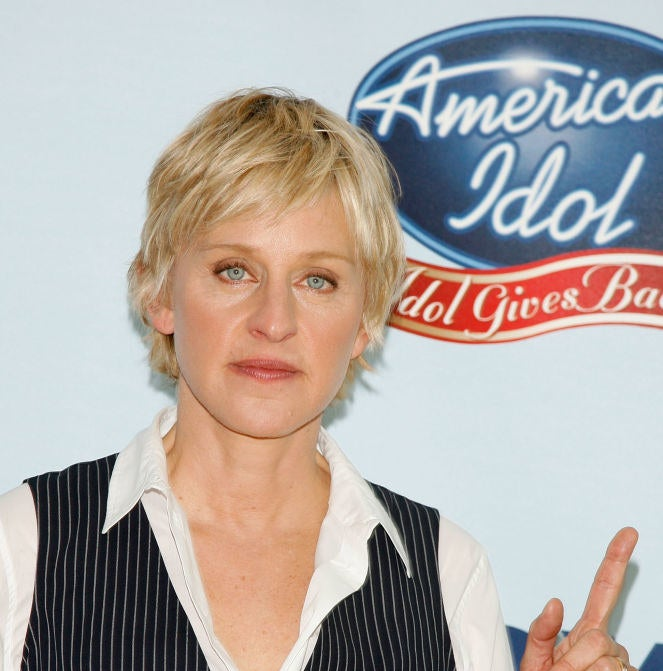 Ellen DeGeneres pointing at the American Idol: Idol Gives Back sign on the red carpet for the event.