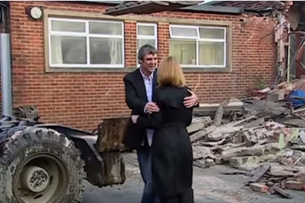 Eddie and Rachel standing outside the destroyed school building
