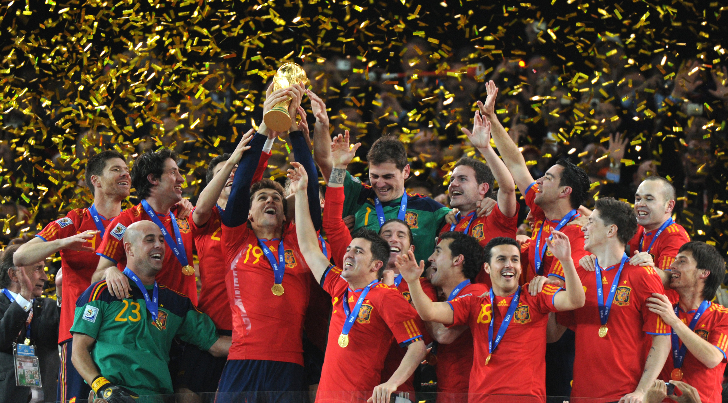 Photo of the Spanish team holding up the World Cup trophy with gold confetti falling around them.