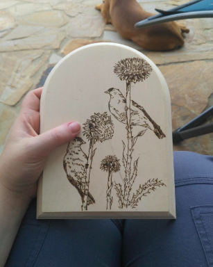 A reviewer holding an arched piece of wood with an engraving of two birds resting on plant stems