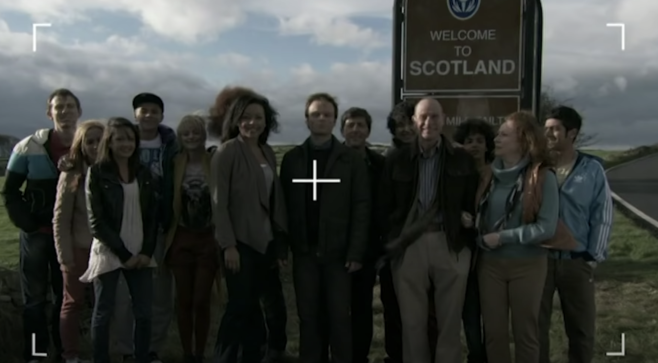 A group photo of the children and students in front of the 'Welcome to Scotland' sign