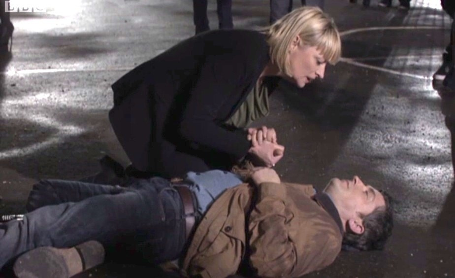 Christine holding Mr Clarkson's hands as he lies on the ground
