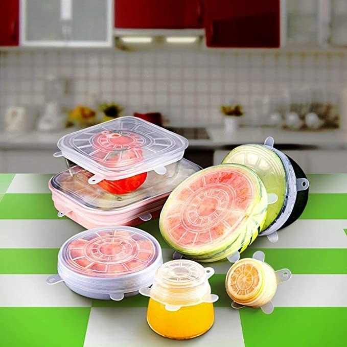 Containers, bowls, mugs and fruits of various sizes being covered with the silicone lids.
