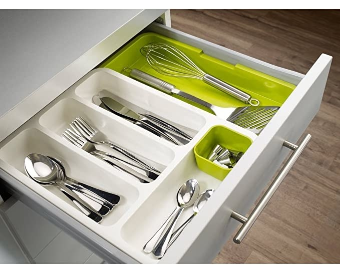 Forks, spoons and knives neatly arranged with the cutlery tray in a kitchen drawer.