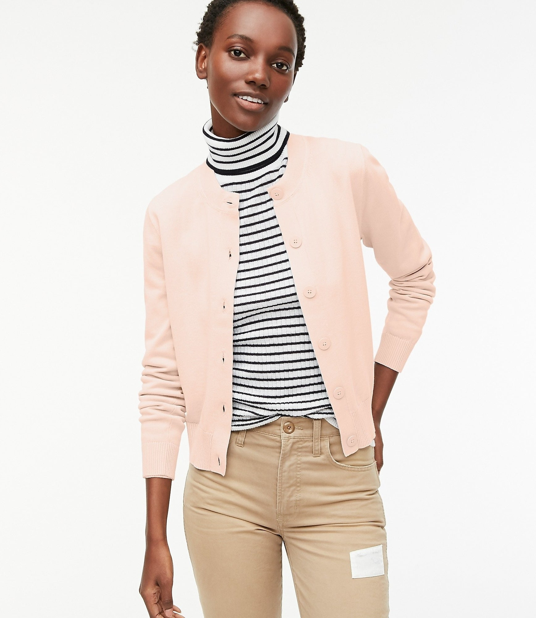 model in blush pink cardigan with round neck and big buttons