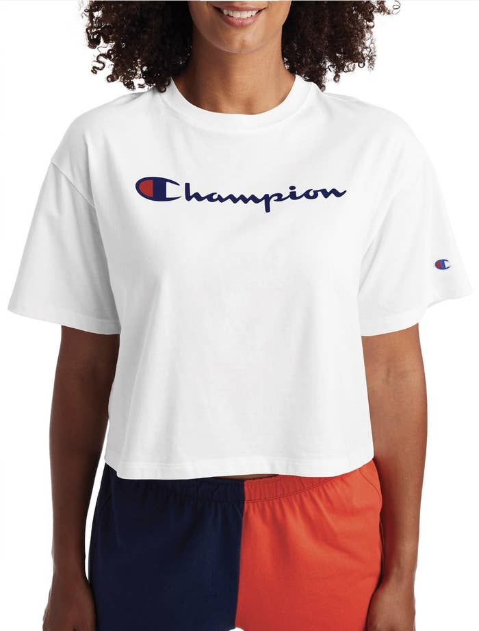 Model in the white T-shirt with Champion written across the chest