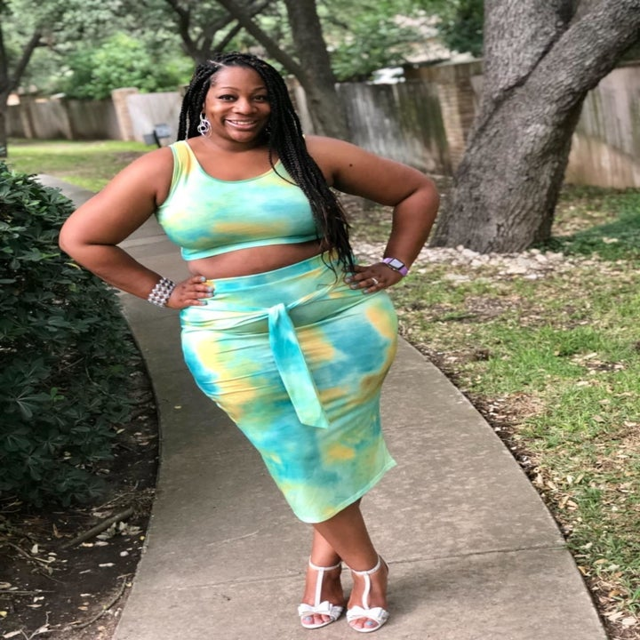 Reviewer wearing the crop tank top and bodycon midi skirt with a tie around the waist in green, blue, and yellow tie-dye