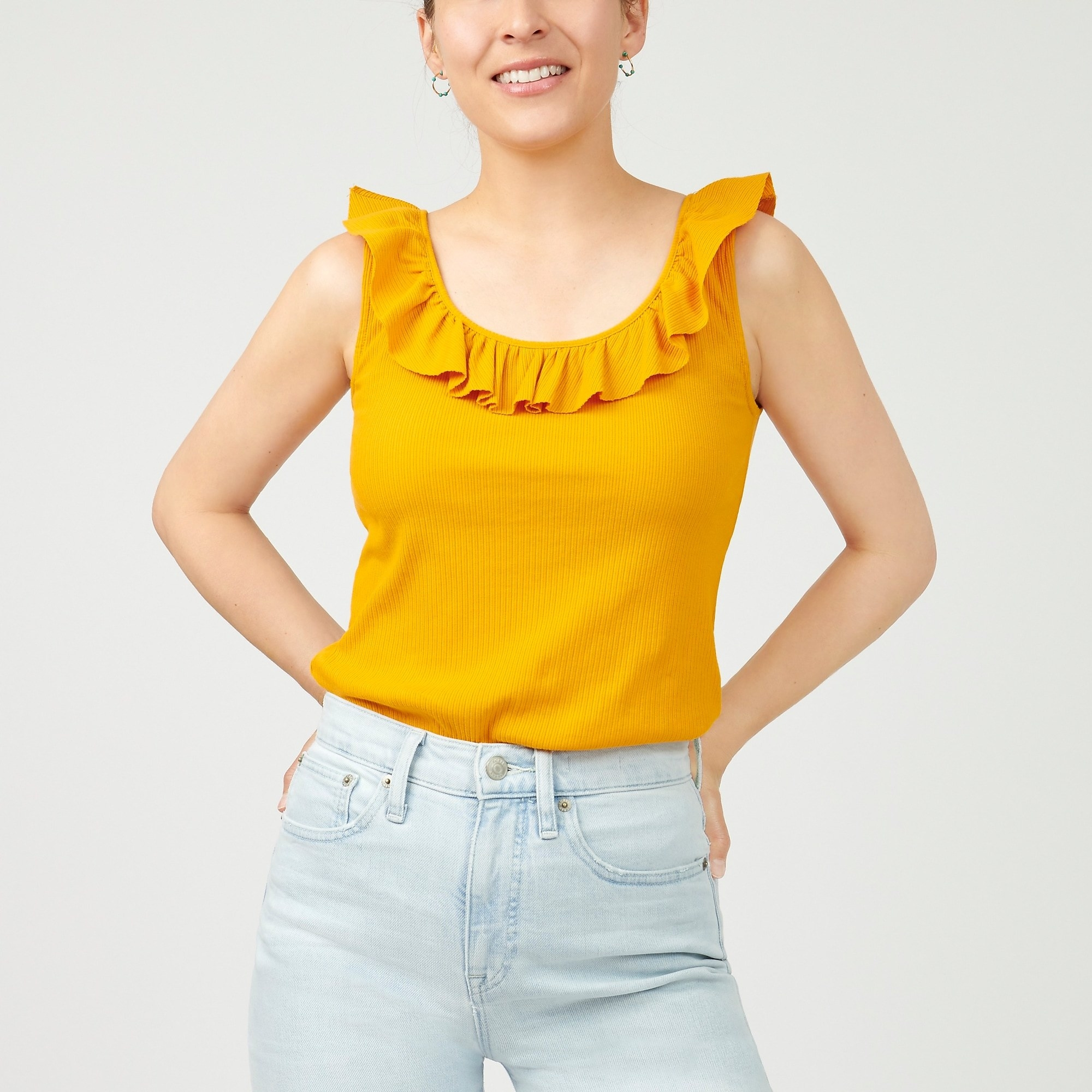 model in yellow tank with ruffle along the neck and sleeves