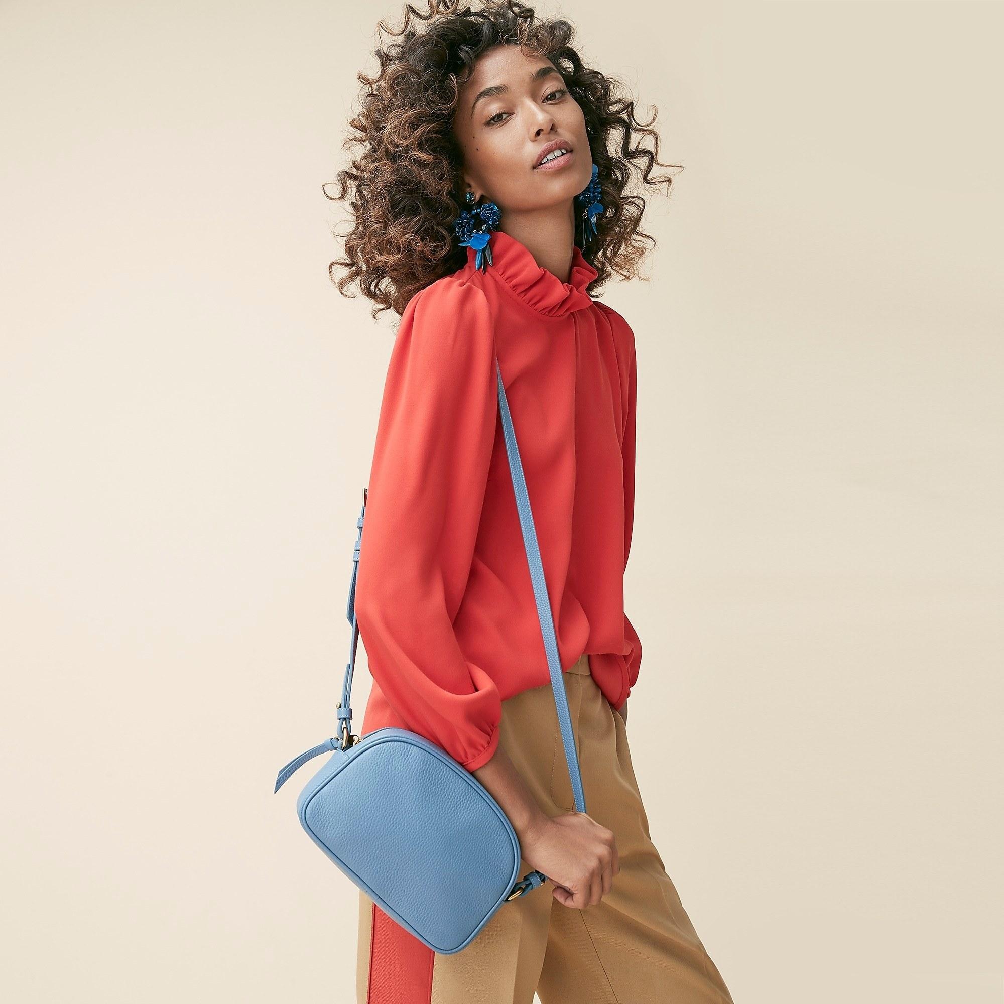 model with blue leather bag with long strap