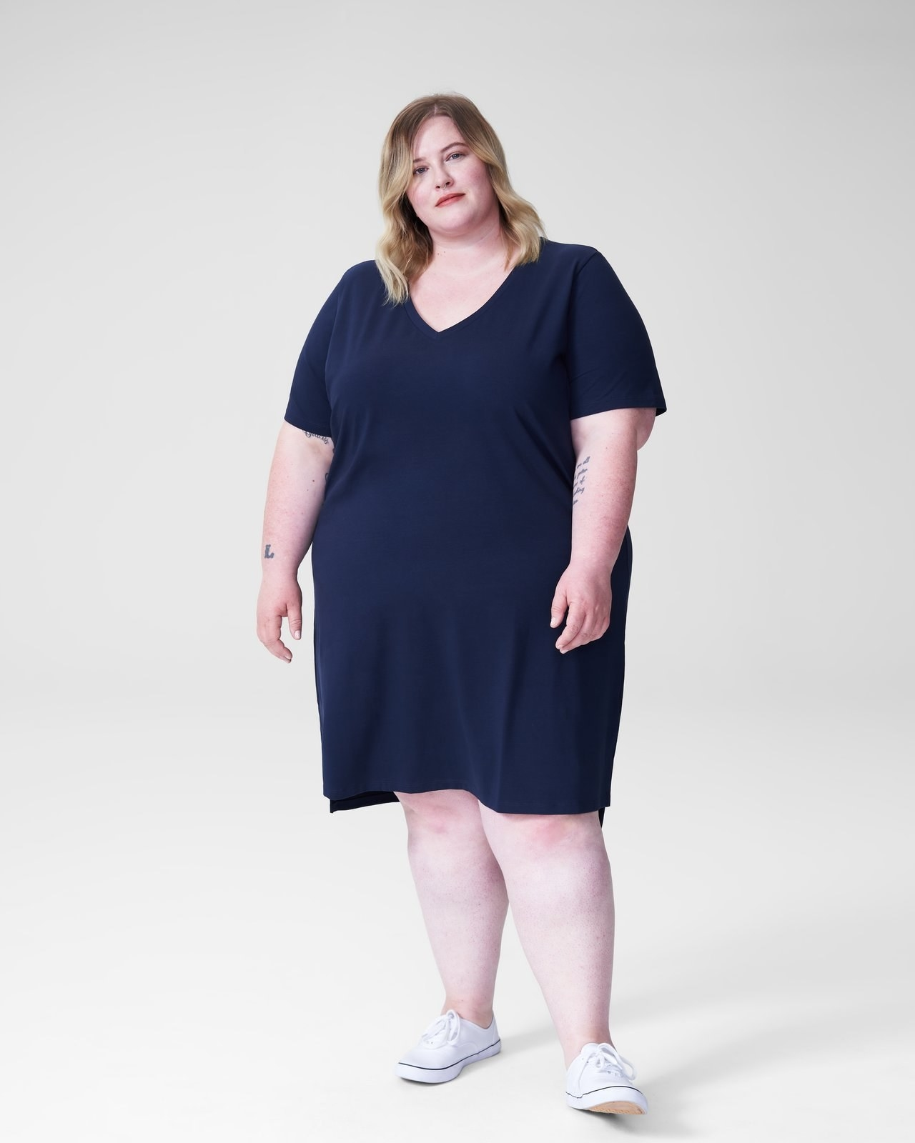 Model wearing the short-sleeved t-shirt dress with a v-neck in navy