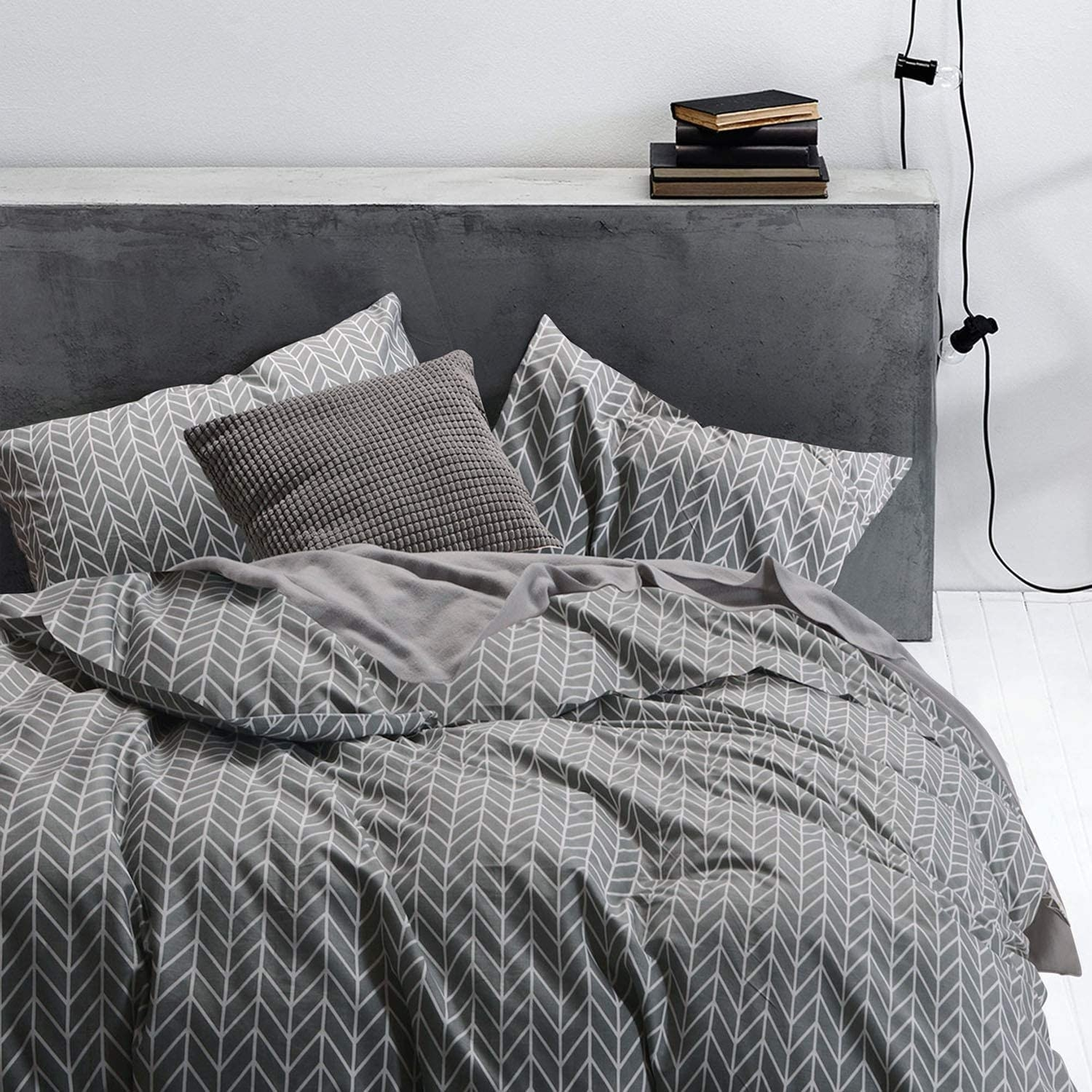 A bed dressed with the sheets is artfully messy in a minimalist bedroom