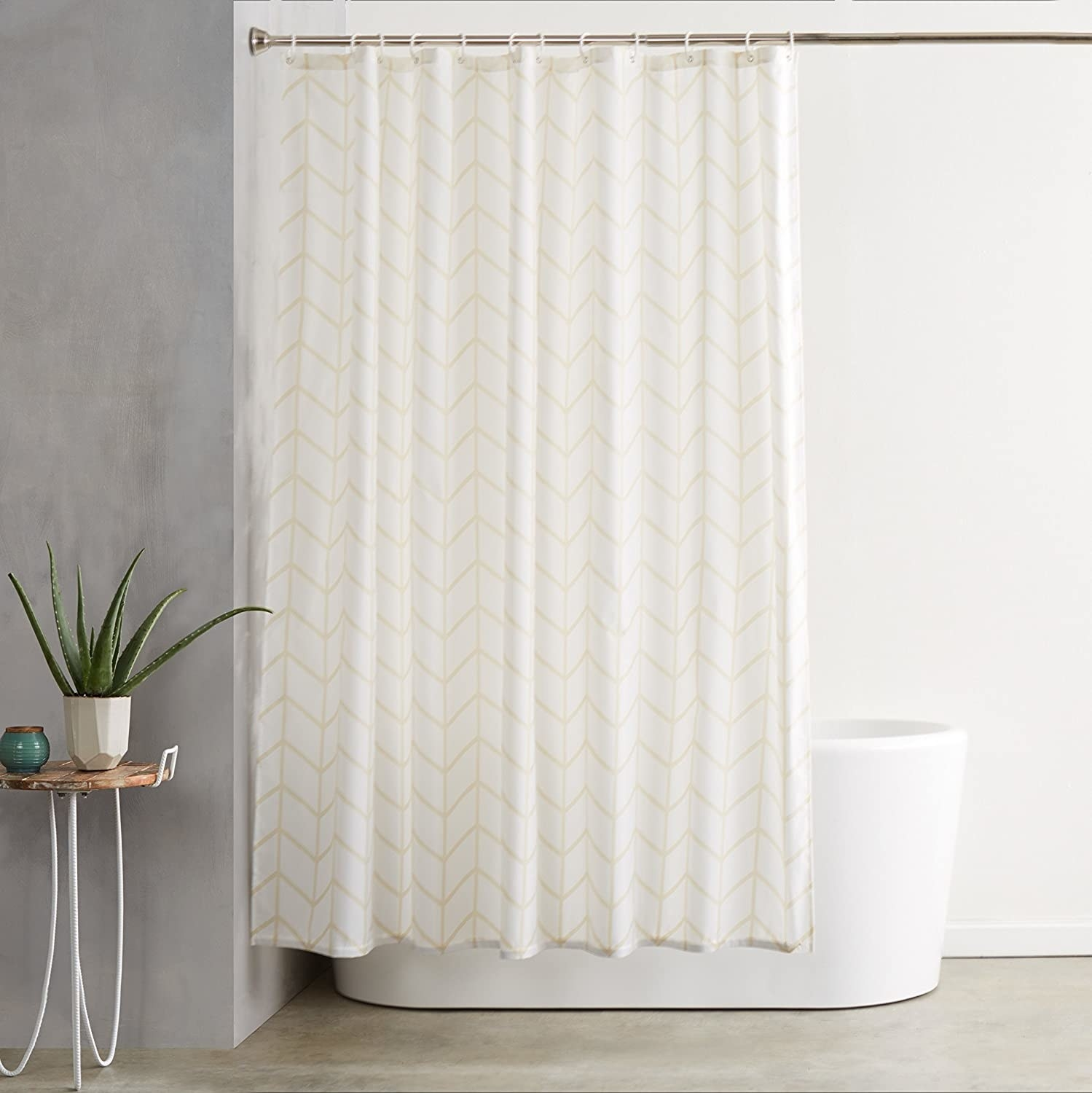 The shower curtain hung over a freestanding tub in a minimal bathroom