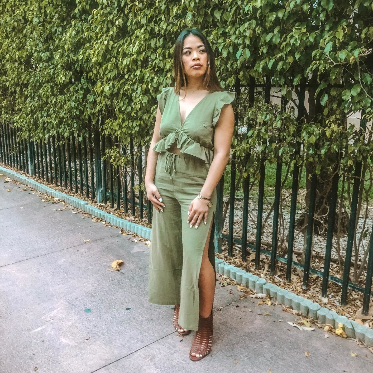 Reviewer wearing the set with pants with elastic waist and high slit on either side of the leg and  the top with a deep v-neck and ruffles along the hem and shoulders in green