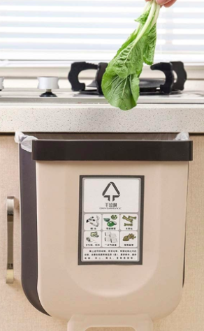 Hand places piece of lettuce in a nude foldable trash can on the side of a sink