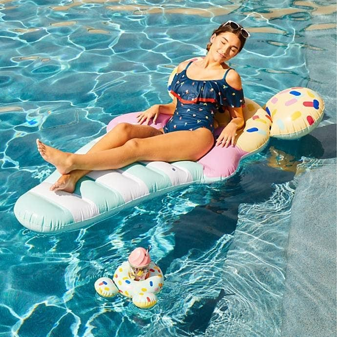 A model sitting in a pool on the float, which is shaped like an ice cream cone with Mickey ears