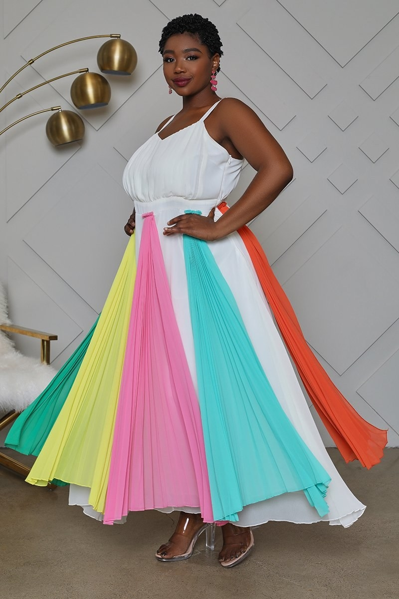 Model wearing the maxi dress with a white top and brightly-colored pleated fabric on the skirt