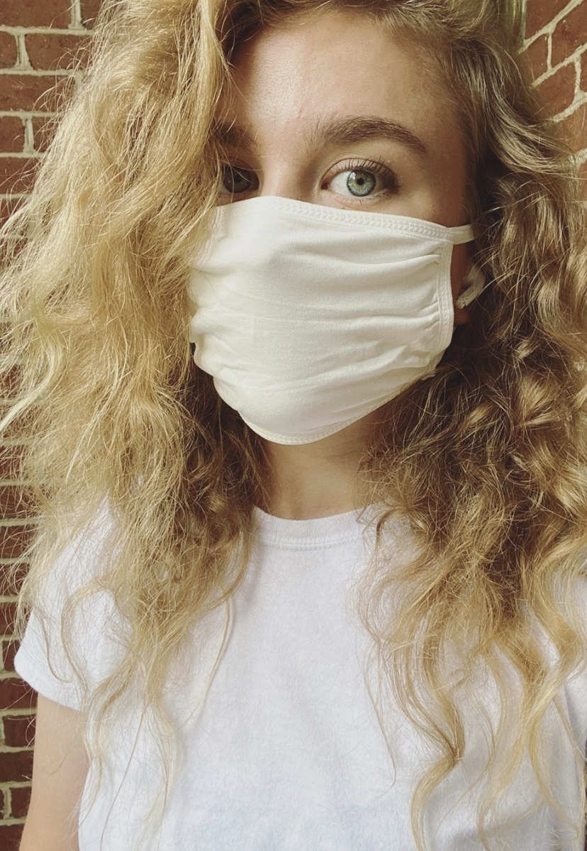 A BuzzFeed editor in a white cotton face mask