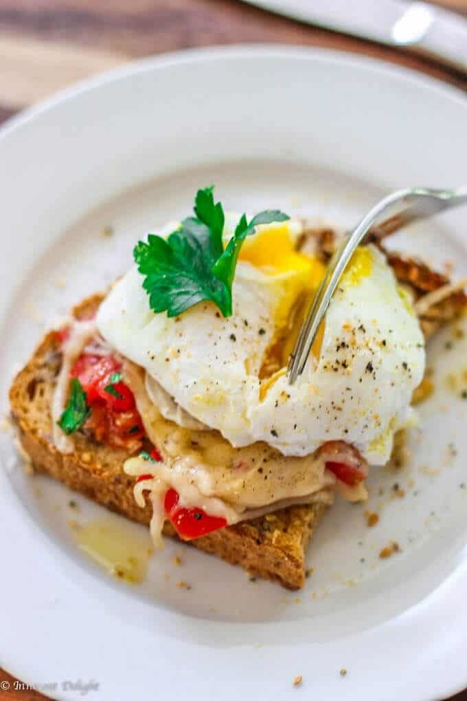 A fork cutting into a poached egg on top of a slice of tomato and cheese toast