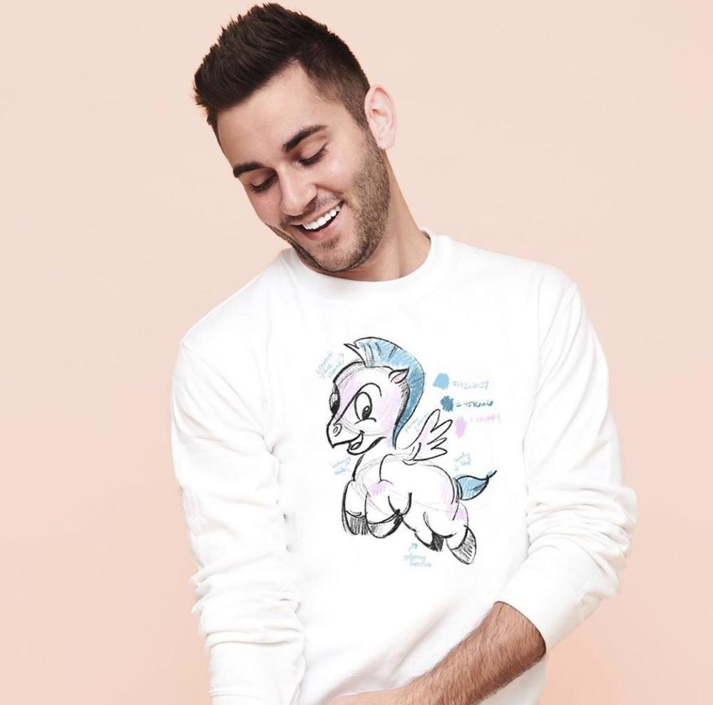 a model wearing a white sweatshirt with an illustrated drawing of baby pegasus on it