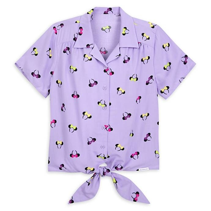 The light purple, short-sleeve top with black ear headbands wearing pink, purple, and yellow bows