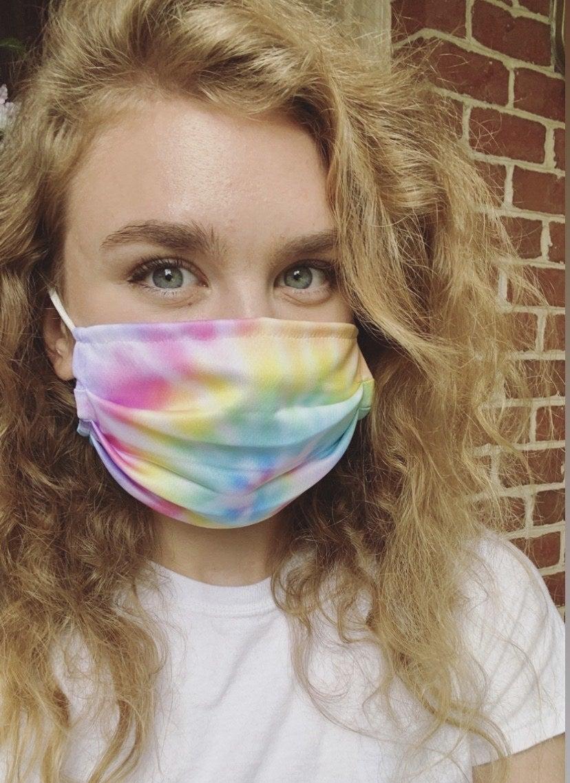 A BuzzFeed editor in a pastel tie dye rainbow mask