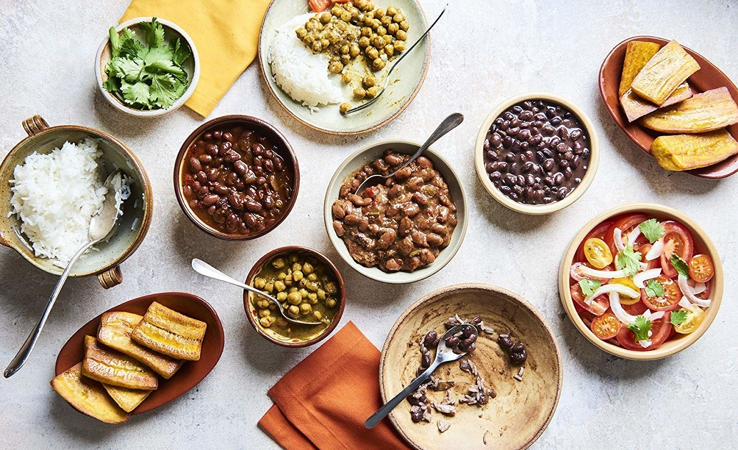 A dinner laid out on a table including A Dozen Cousins ready to eat seasoned beans.